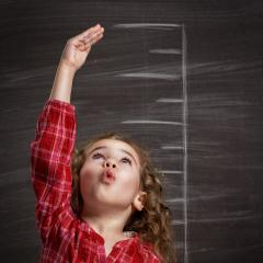 Girl measuring herself - why people grow to different heights. Credit: Shutterstock/Yuganov Konstantin.