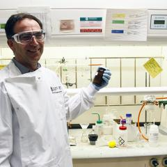 Dr Mark Blaskovich holding a vial in front of a fume hood